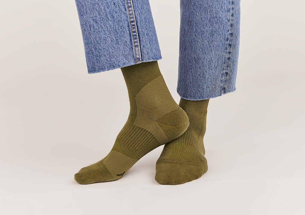 A pair of feet wearing olive travel compression socks.