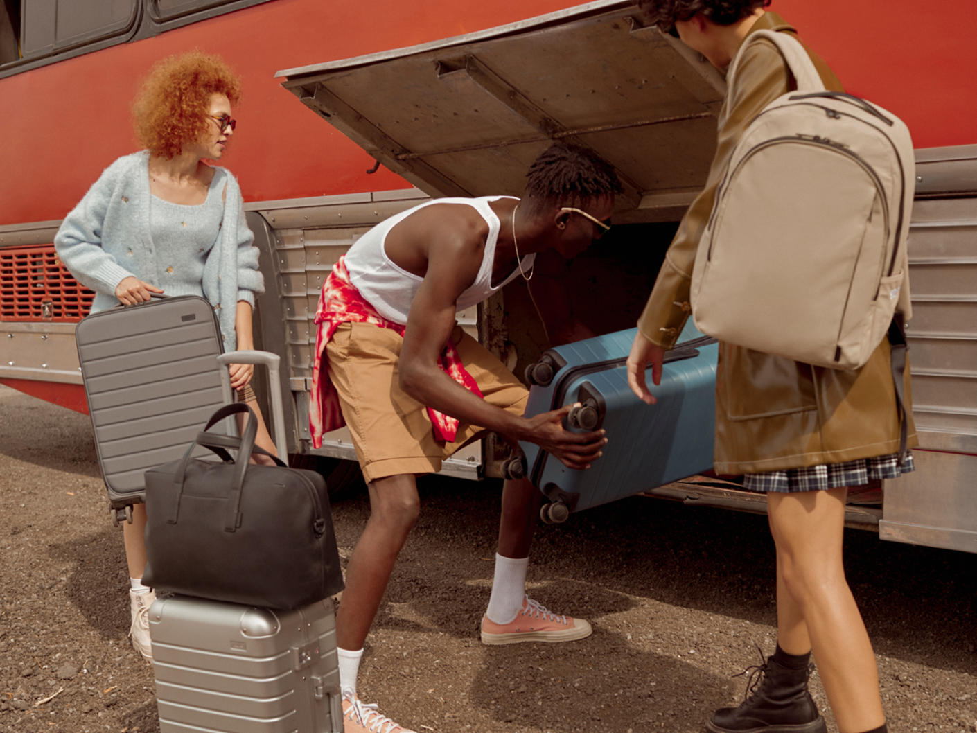 Suitcases being put into the luggage compartment of a bus by three travelers.