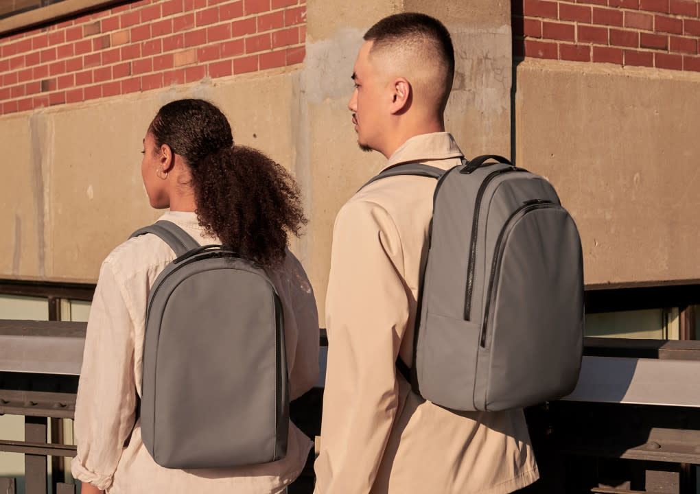 Two people wearing the Daypack and the Backpack in asphalt shown from behind.