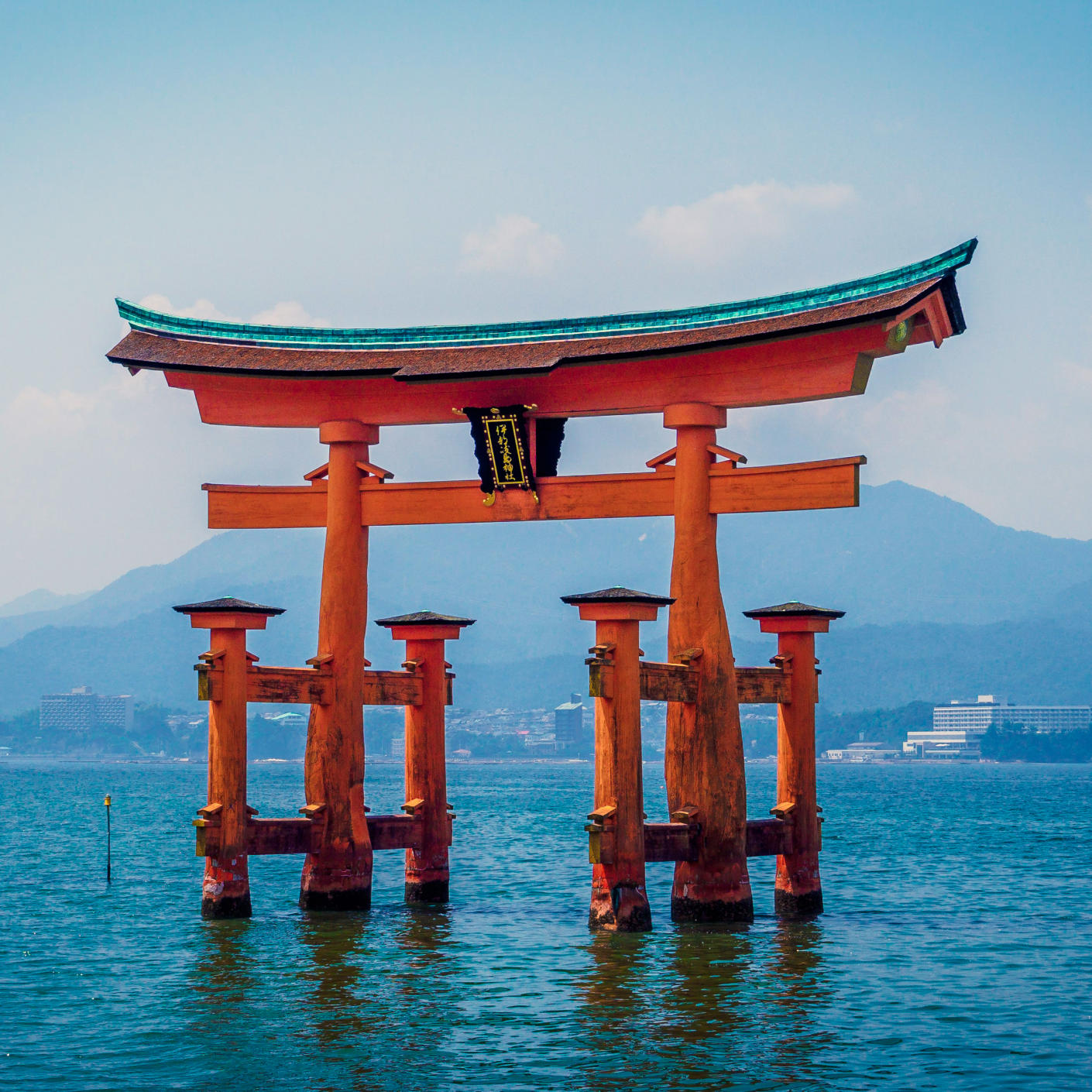 Japanese shinto Itsukushima Shrine in orange partially submerged in water set amidst a mountain backdrop.
