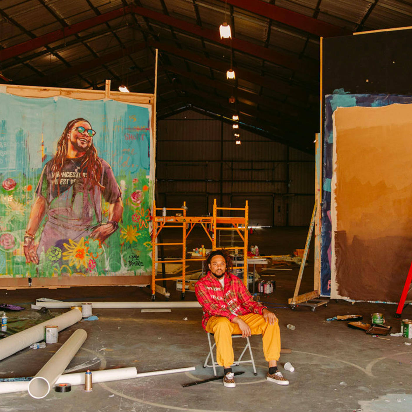 Artist at the forefront sitting on a chair in front of large paintings