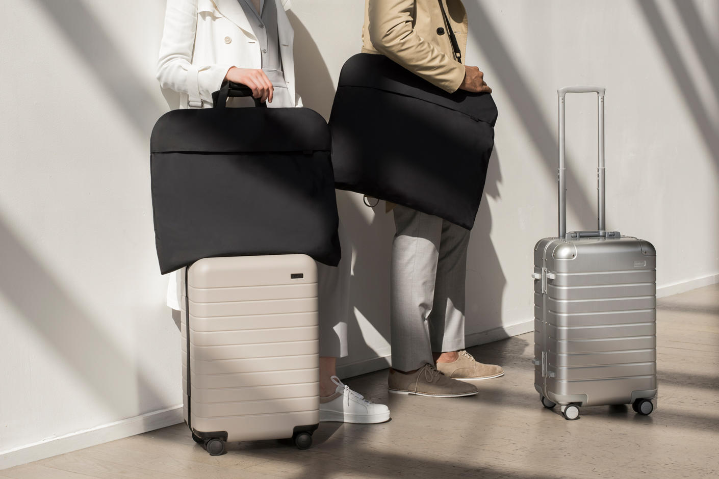 Two people standing in front of a white wall.  One person is standing with The Bigger Carry-On in Sand with The Signature Garment Bag in Black attached to the top.  The other person is standing while holding The Signature Garment Bag in Black over their shoulder with The Aluminum Bigger Carry-On in front of them.