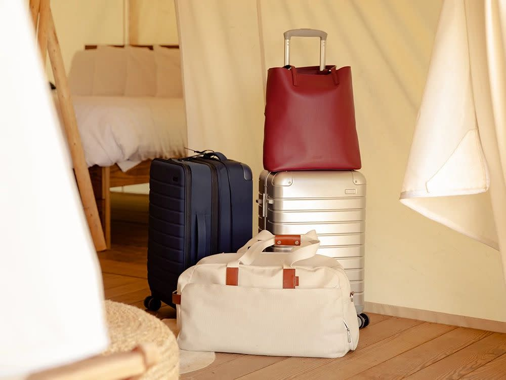 A navy softside carry-on, a silver aluminum carry-on with a red tote bag on top, and a canvas weekender bag in a bright outdoor tent.