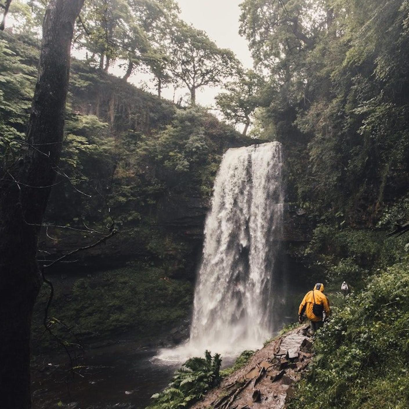 A man in a yellow jacket hiking towards a waterfall in the UK.