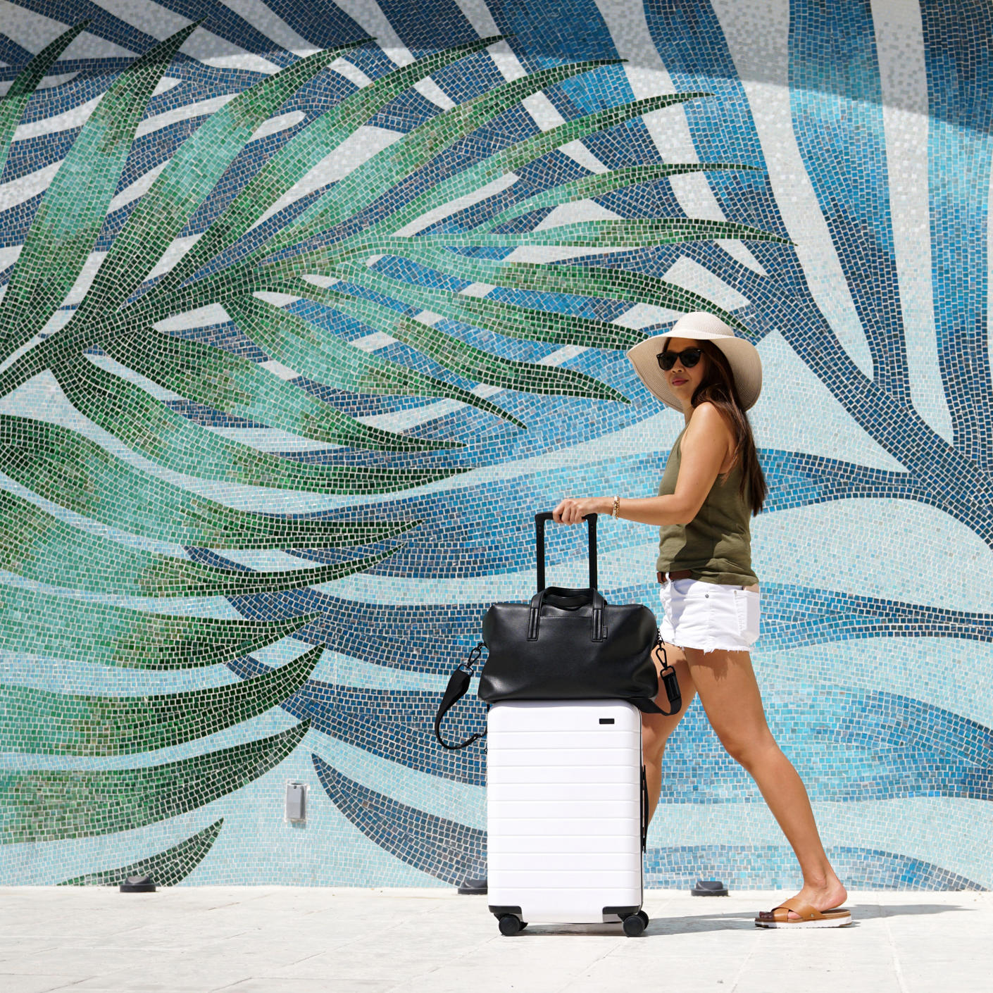 A woman in white shorts and a white Away bigger carry on suitcase and black Everywhere bag walking in front of a palm leaf mosaic.
