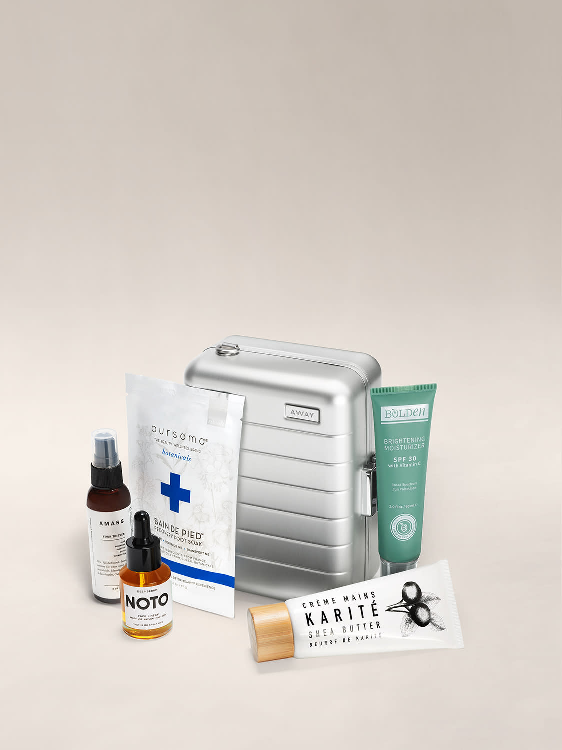 Mini suitcase in aluminum silver shown behind a bottle of hand sanitizer, foot soak, face serum, SPF 30 moisturizer and hand cream.