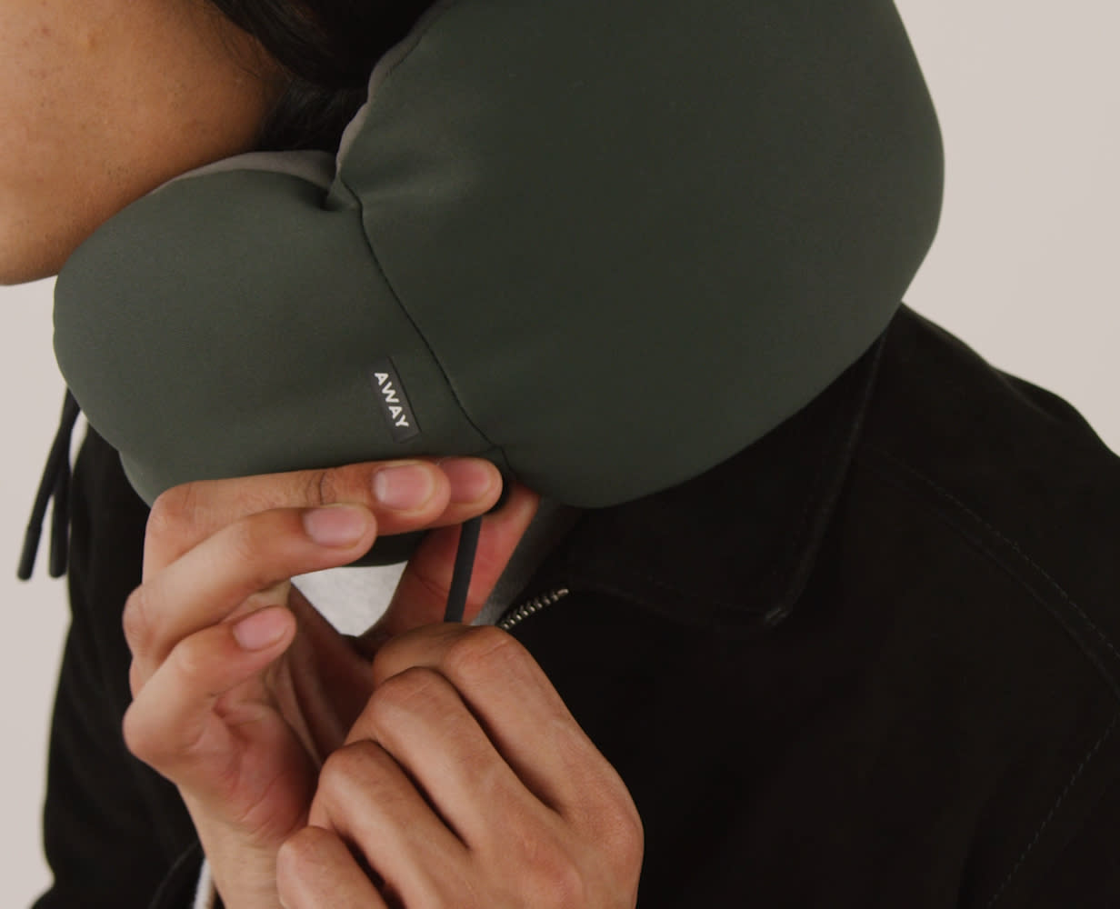A person adjusting their Away travel neck pillow in green for comfort.