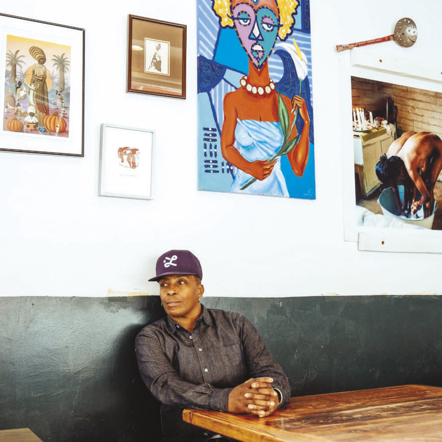 An Oakland chef sitting in a booth against a wall displaying modern art.