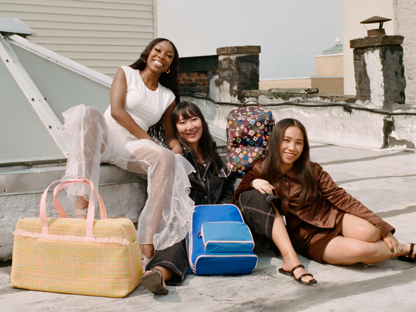 Away designer collab group shot including Tia Adeola, Ji Won Choi and Sandy Liang with their uniquely designed bags