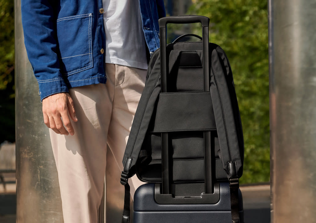 The Backpack in black sitting on top of navy suitcase secured by a sleeve that attaches the Backpack to the suitcase handle.