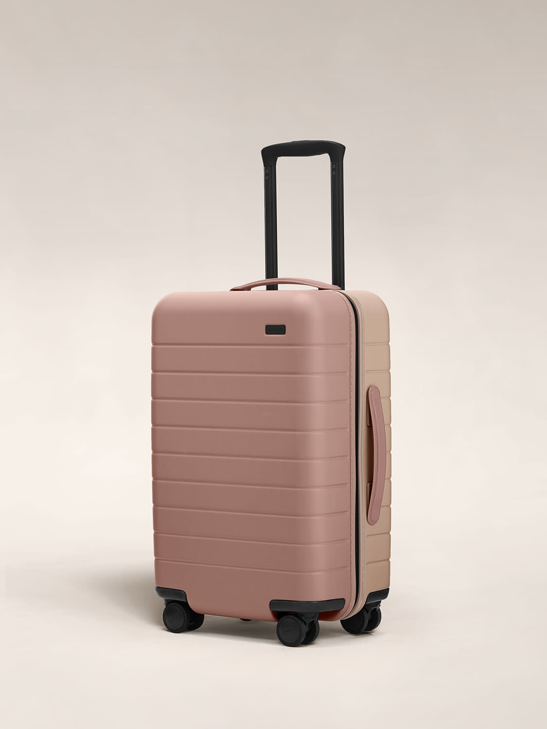 Angled view of The Carry On hardside suitcase in Dusty Rose/ Taupe