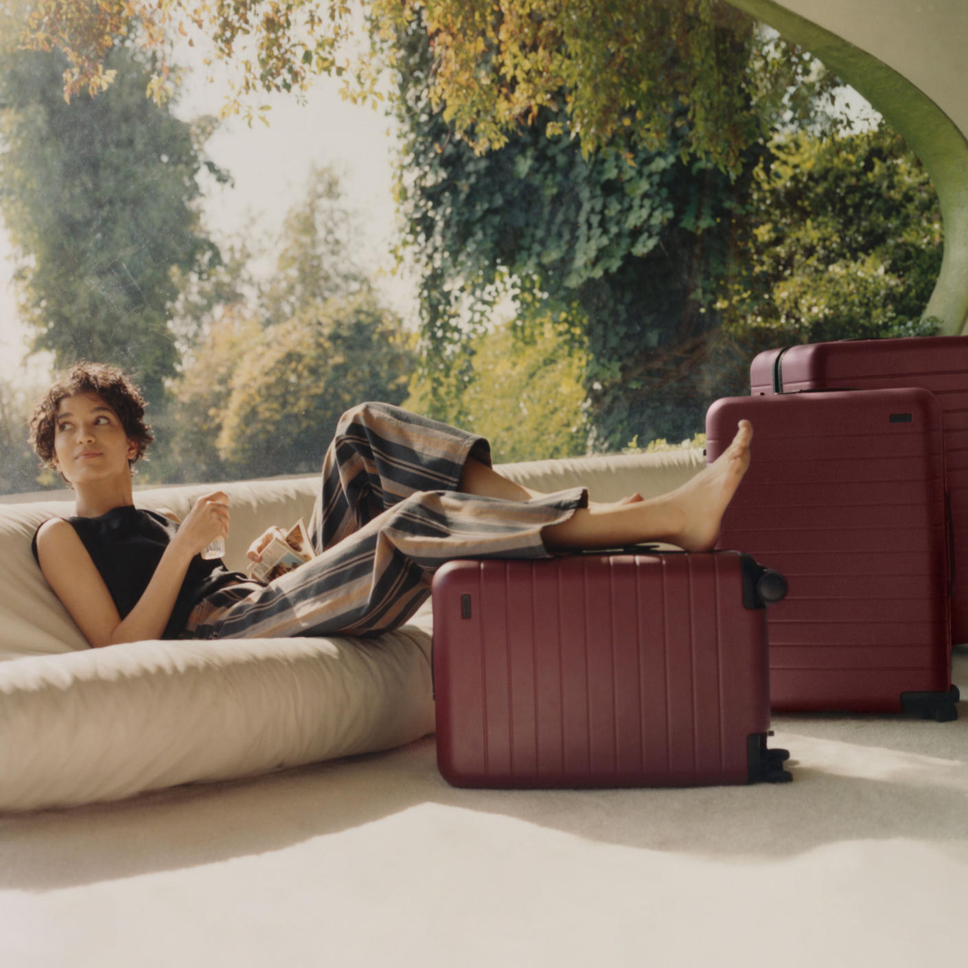 A woman lounging on a sofa ready to travel with her carry-on and checked Away luggage in maroon, at her feet.