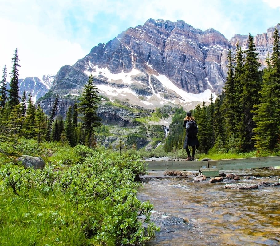 A woman hiking, looking at a mountain summit with a creek flowing and pine trees around her.