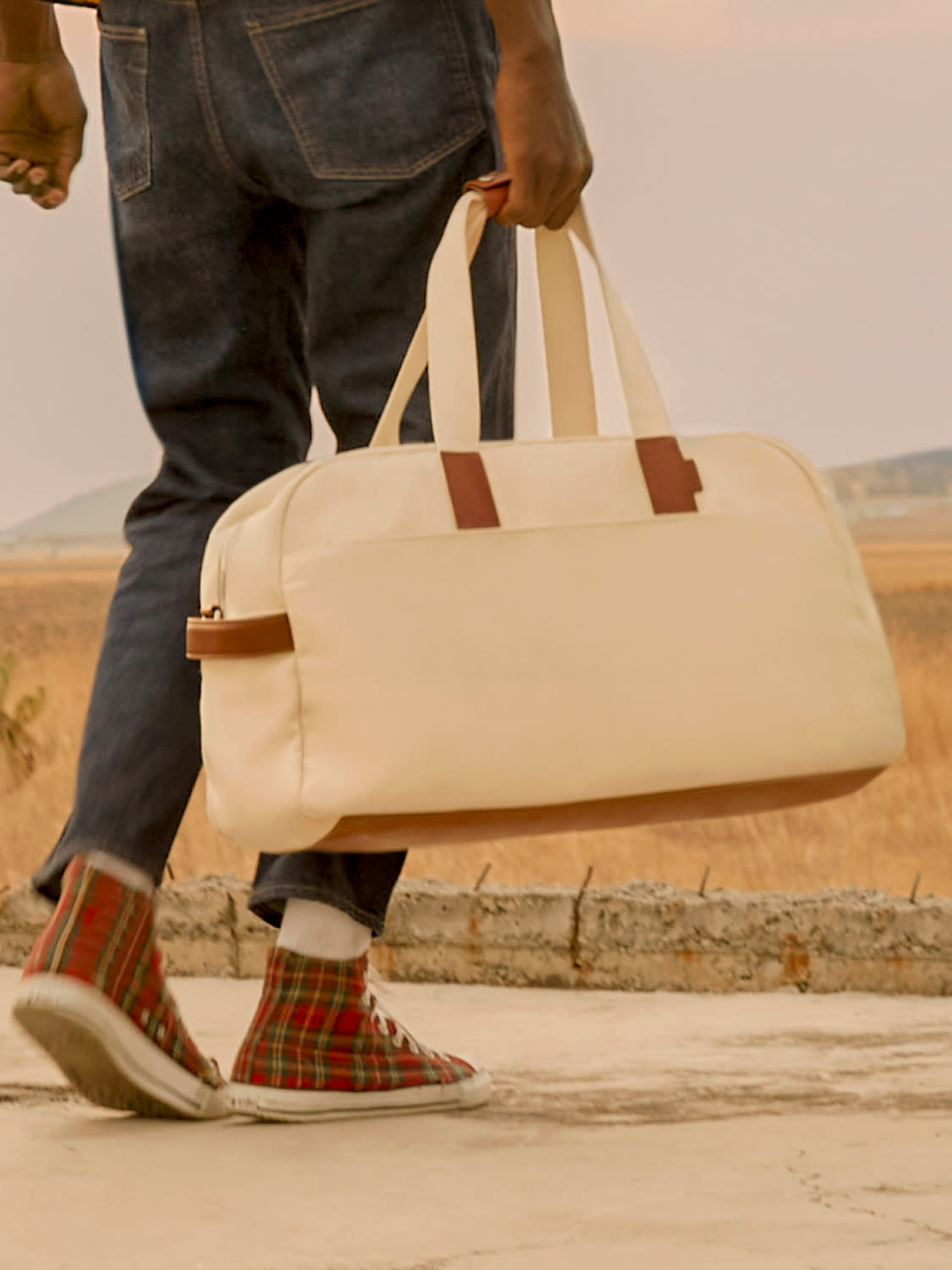 A man carrying a duffle bag, The Weekender by Away in natural canvas.