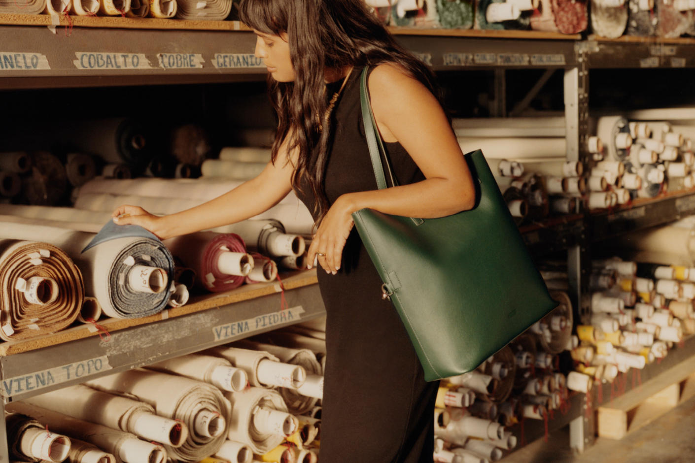 A woman in a black dress looking at some rolls of cloth with a green tote shoulder bag.