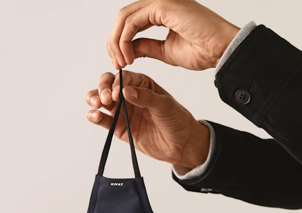 A pair of hands with cuffs of a jacket shown adjusting an Away reusable cloth face mask.