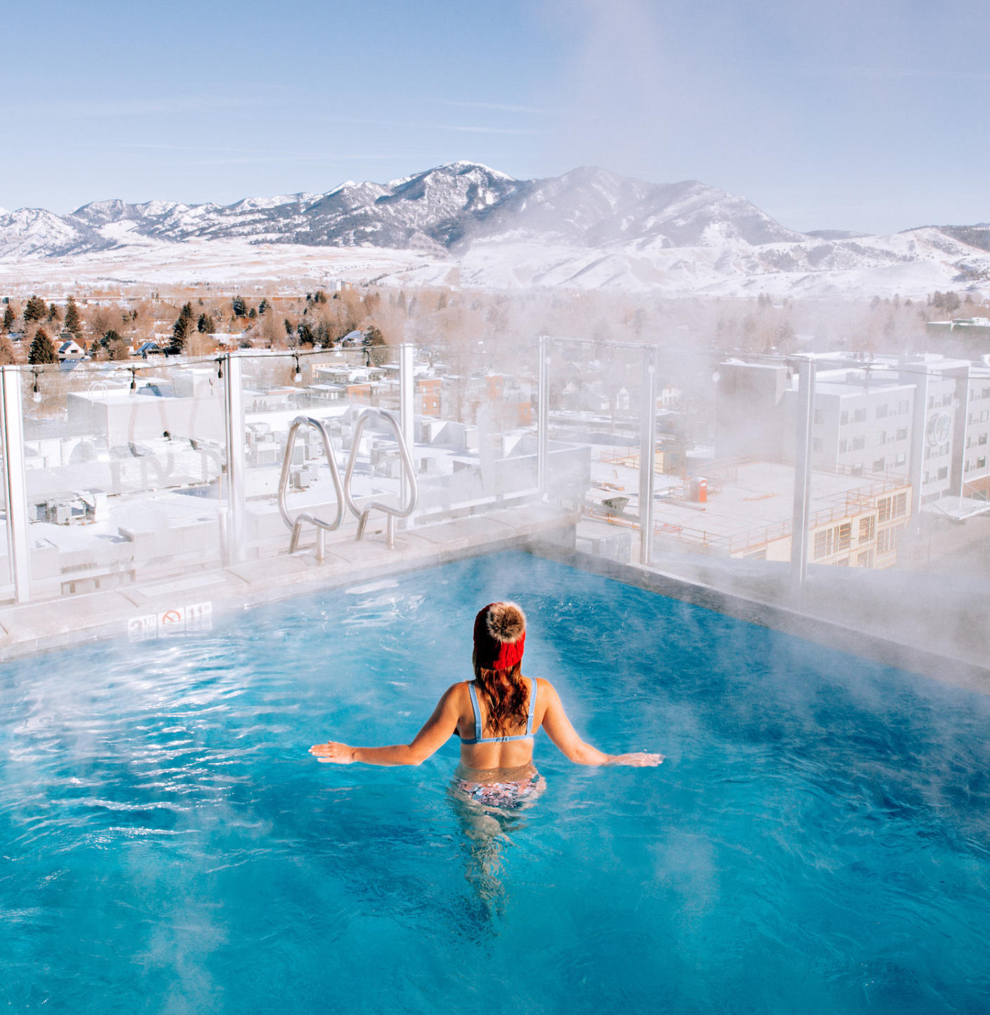 A woman in a hotel rooftop pool overlooking the rocky mountains of Montana.