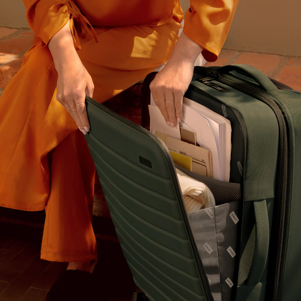 A person packing documents into the front pocket of a softsided carry-on suitcase from the Away Expandable collection.