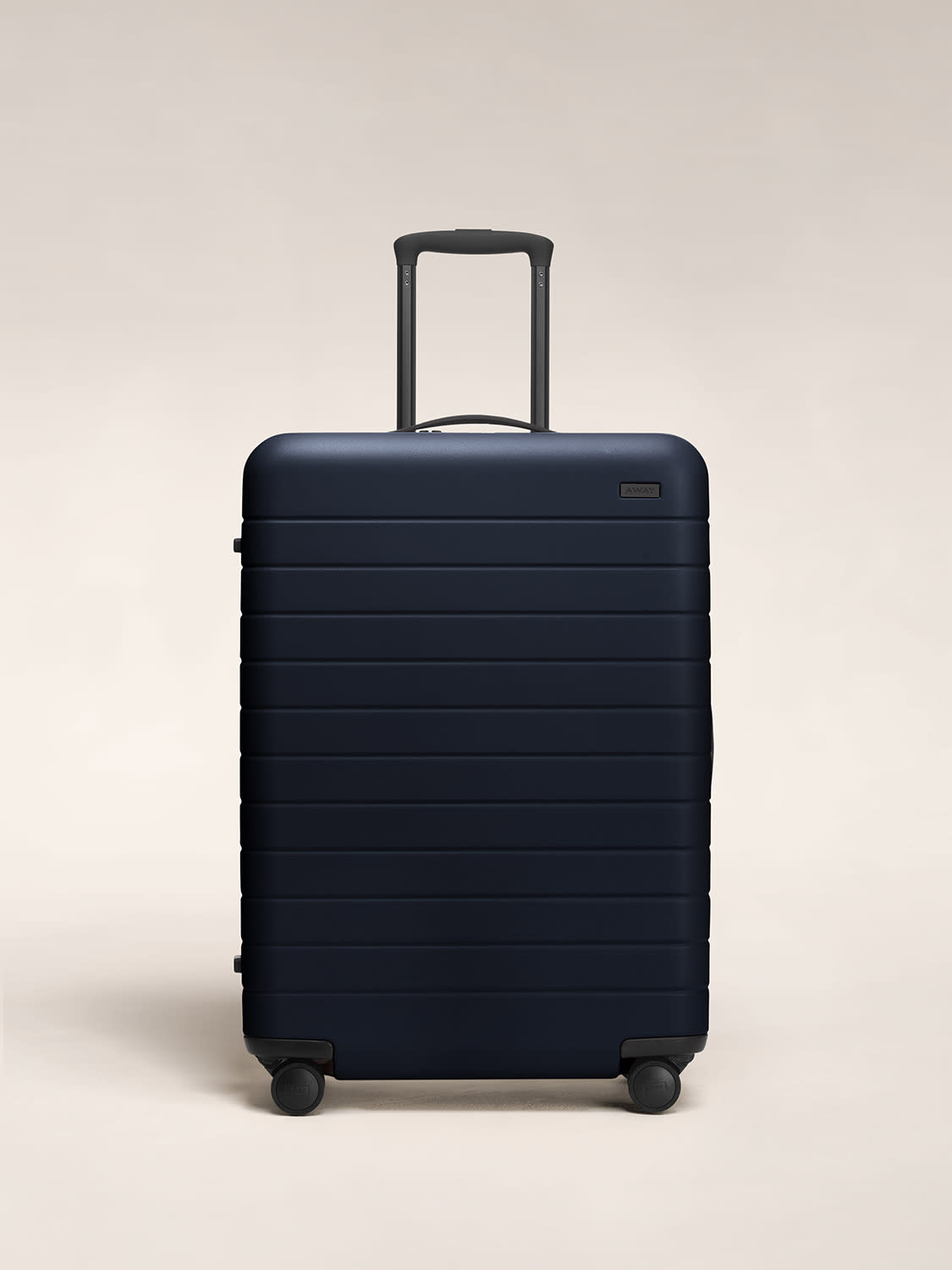 Front view of The Medium hardside luggage in Navy