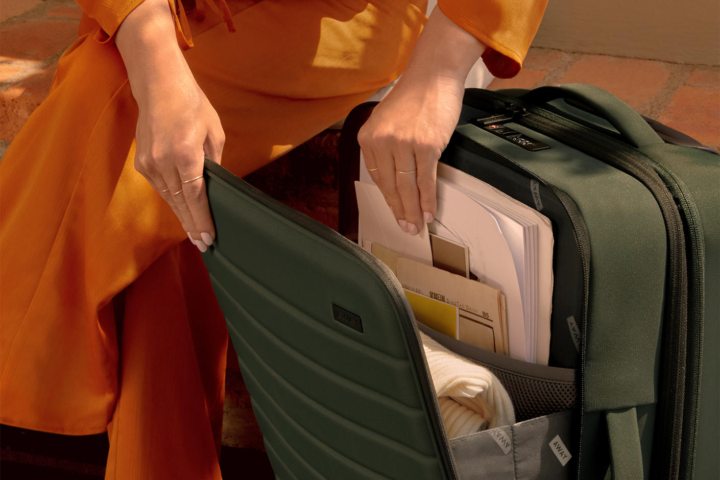 A woman using her hands to browse through the documents in the front pocket of her green softsided carry-on suitcase.