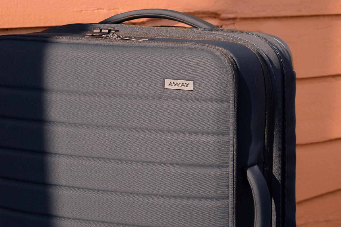 Top portion of a grey Away softsided carry-on suitcase.
