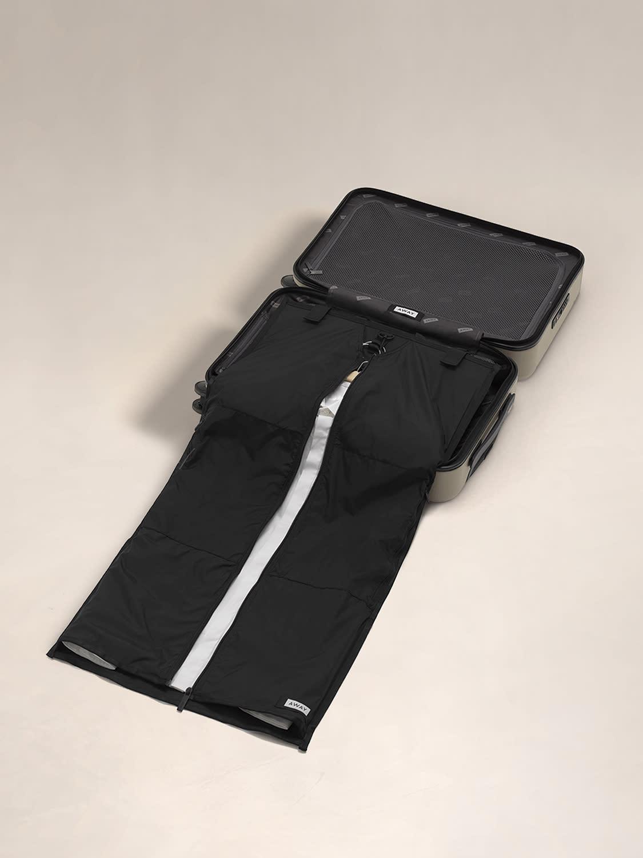 A garment sleeve open inside an open suitcase.