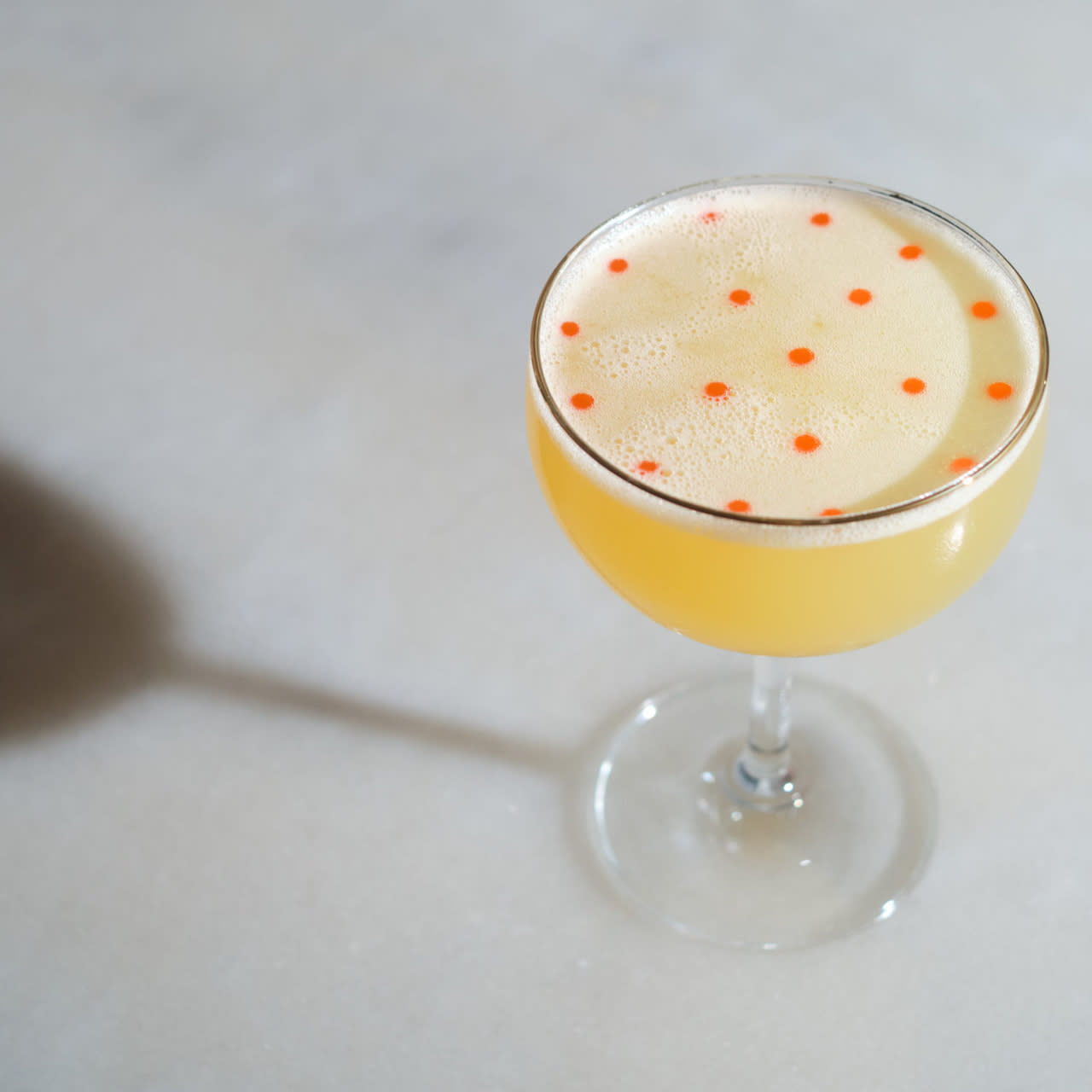 A cocktail drink displayed in a glass, yellow with small orange circles.