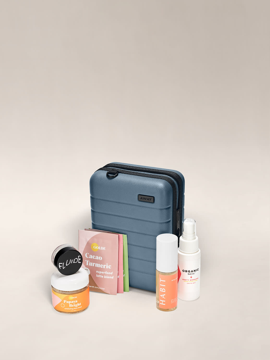 Mini suitcase in coast shown behind a bottle of touchless SPF mist, hand sanitizer, three packs of latte samplers, a facemask and pink glitter.