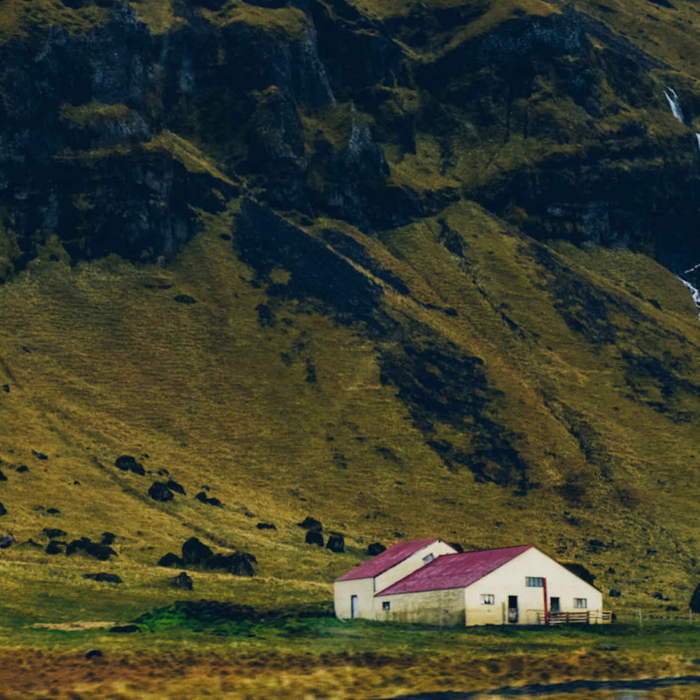 A house at the bottom of a green mountain range in Iceland.