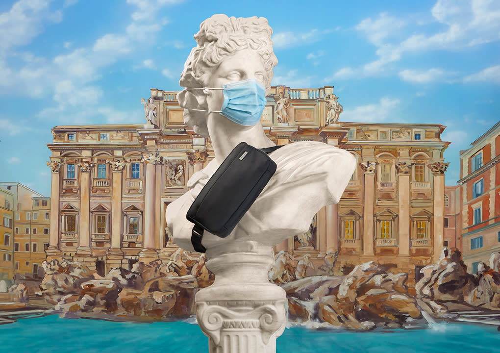 A statue wearing a mask with a black Away sling bag cross bodied against its torso with the Trevi Fountain in the background.