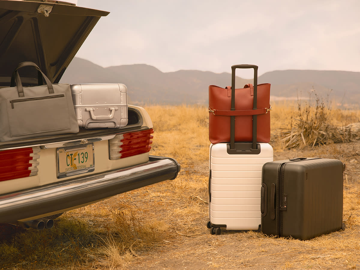 A sedan trunk open with a gray duffle bag and an aluminum suitcase inside, two Away suitcases with a red Tote bag outside on the ground.