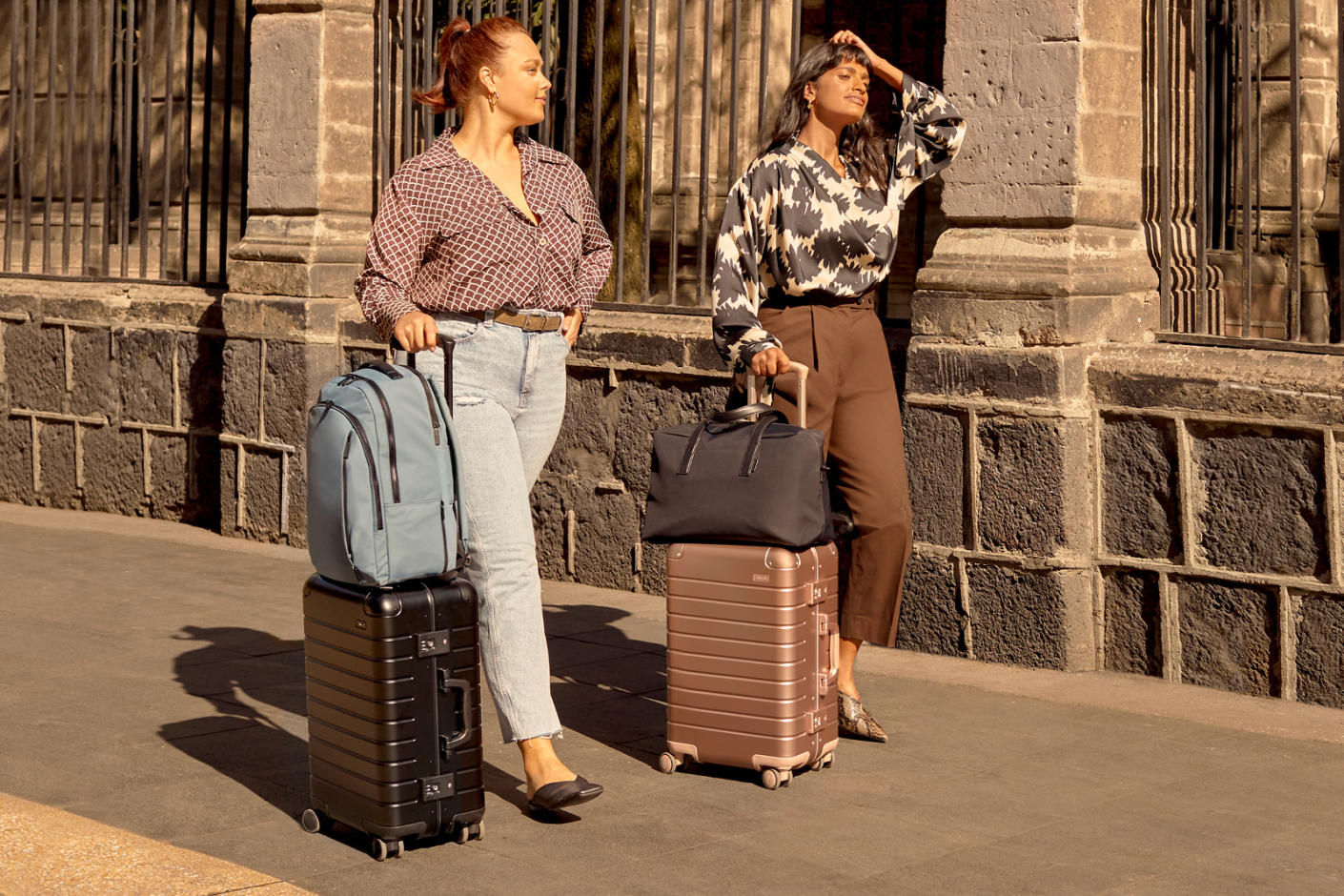 Two women strolling down a street with their travel bags, a backpack and duffle bag paired with aluminum carry-on suitcases.