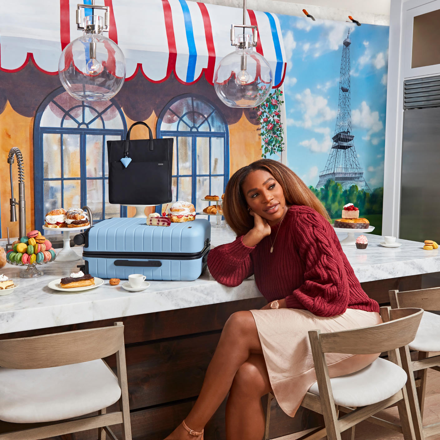Serena Williams sitting in a cafe table with an Away suitcase in light blue on the table.