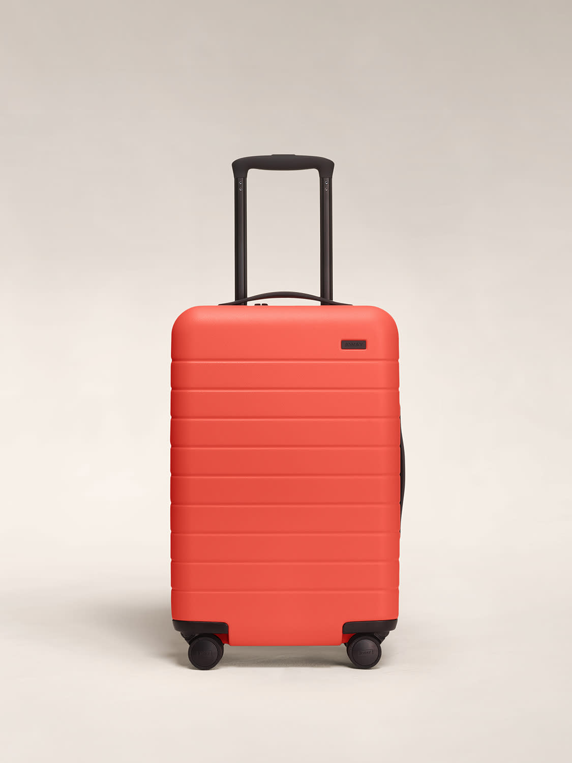 Front view of Away hardside Carry-On sized luggage in Coral