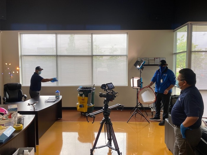 camera crew recording janitor clean office.