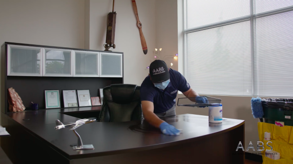 man cleaning office desk with wipe.