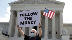 "A man holds up a ""Follow the Money"" sign in front of the U.S. Supreme Court July 9, 2020."