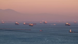 The sunset illuminates the scene of dozens of container ships siting off the coast of the Ports of Los Angeles and Long Beach, waiting to be unloaded