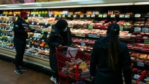 A shopper wearing a surgical mask, center, looks at looks at packaged meats at a Trader Joes in Brooklyn, New York.