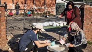 Volunteers prepare portions of porridge to distribute to children for breakfast in Johannesburg