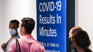 People wearing facemasks enter a COVID-19 testing site at Orlando International Airport.