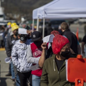 Farmworkers wait in line to receive the Moderna Covid-19 vaccine at a vaccination clinic
