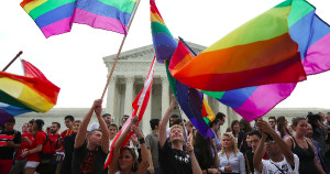 People waving Pride flags in front of the Supreme Court Building