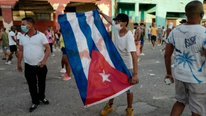 A man waves a Cuban flag during a demonstration against the government of Cuba