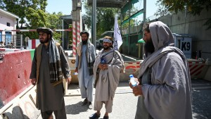 Taliban fighters stand guard at an entrance of the green zone area in Kabul