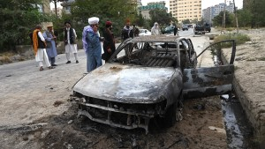 Taliban fighters investigate a damaged car after multiple rockets were fired in Kabul