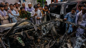 Relatives and neighbors gathered around the incinerated husk of a vehicle targeted and hit by an American drone strike, in Kabul, Afghanistan.