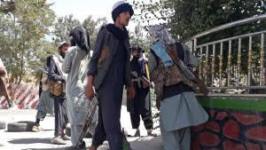 Taliban fighters stand along the roadside in Ghazni