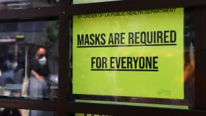 A storefront sign reminds people masks are for everyone