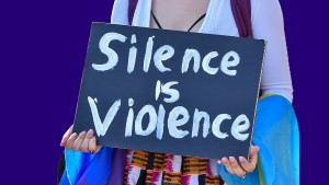 Protester holding silence is violence sign